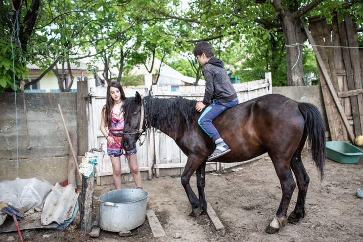 Nicoletta and her brother Andrei play with a horse at their grandparents' farm.