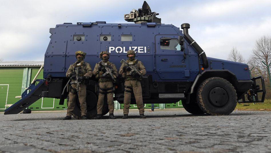Bewaffnete Polizisten des SEK bei der Präsentation des Panzerwagens