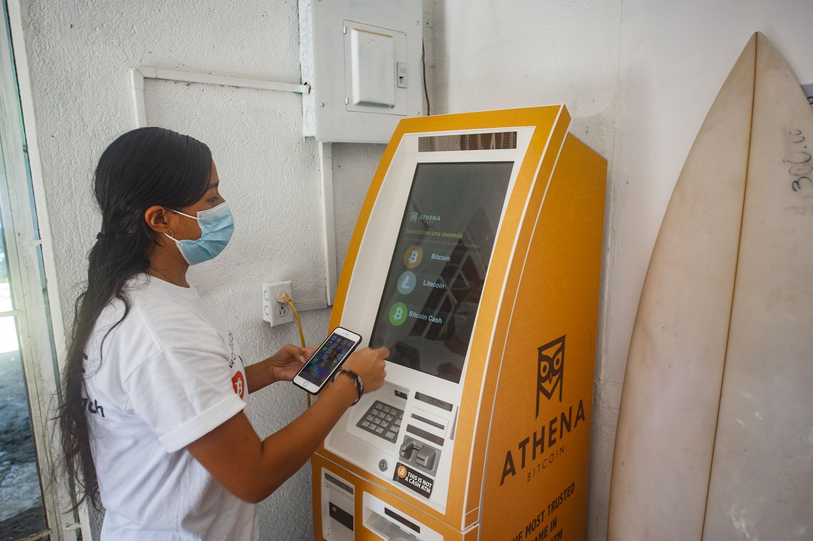 A woman withdraws money from a Bitcoin ATM. Salvadoran