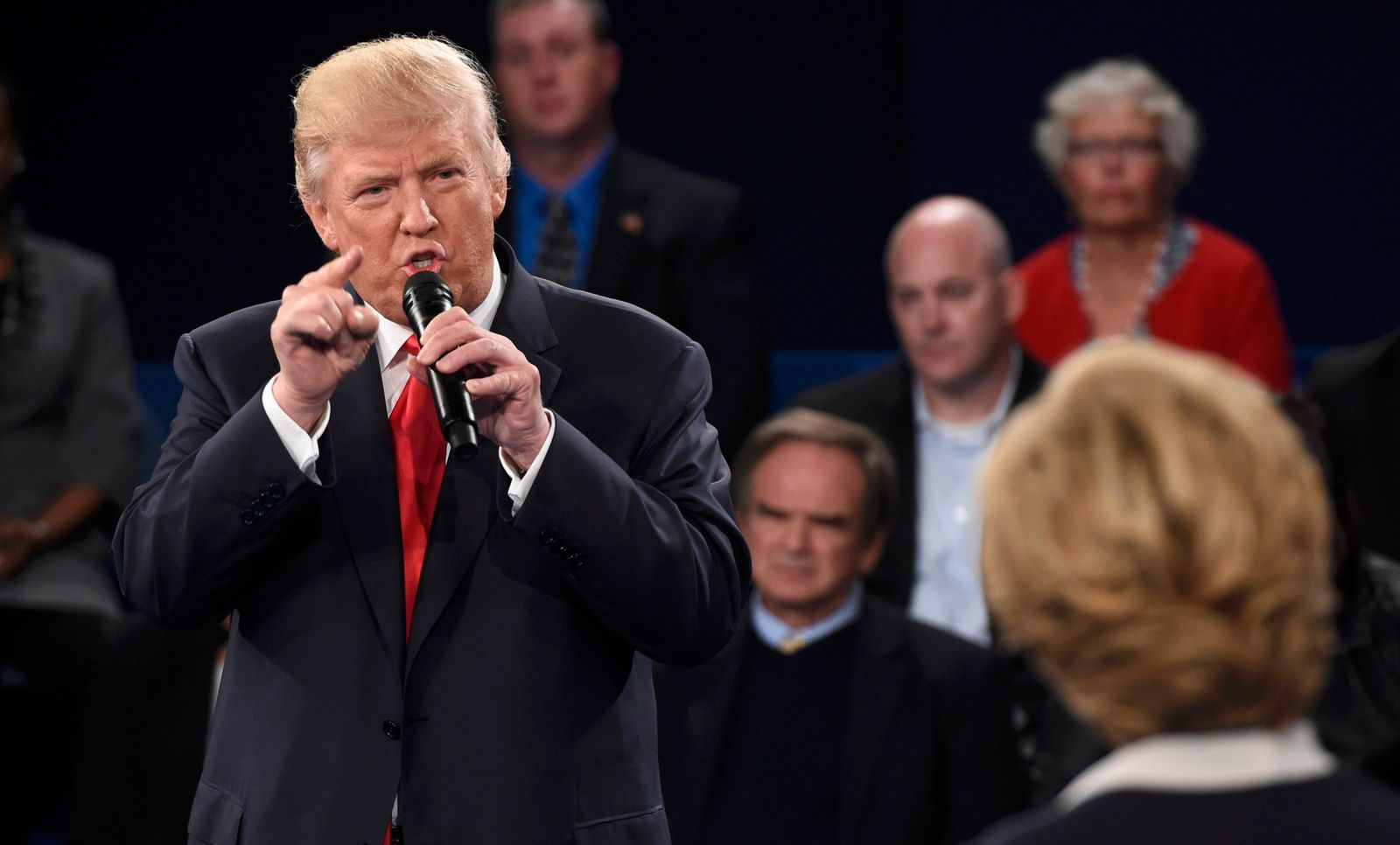 Republican U.S. presidential nominee Trump speaks as Democratic U.S. presidential nominee Clinton listens during their presidential town hall debate in St. Louis