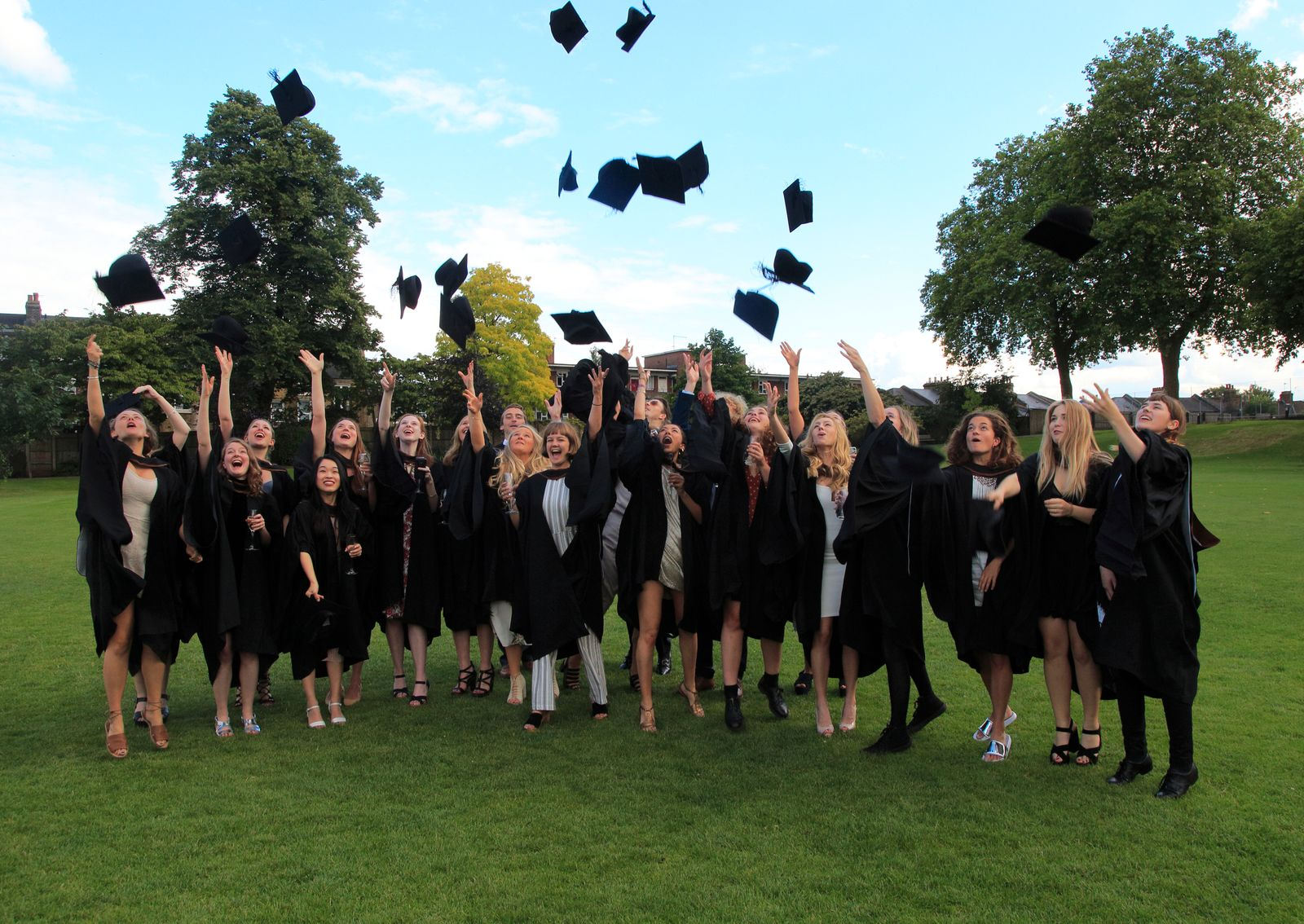 Graduates in gowns throwing their mortarboards into the air, Goldsmiths, University of London, England, UK