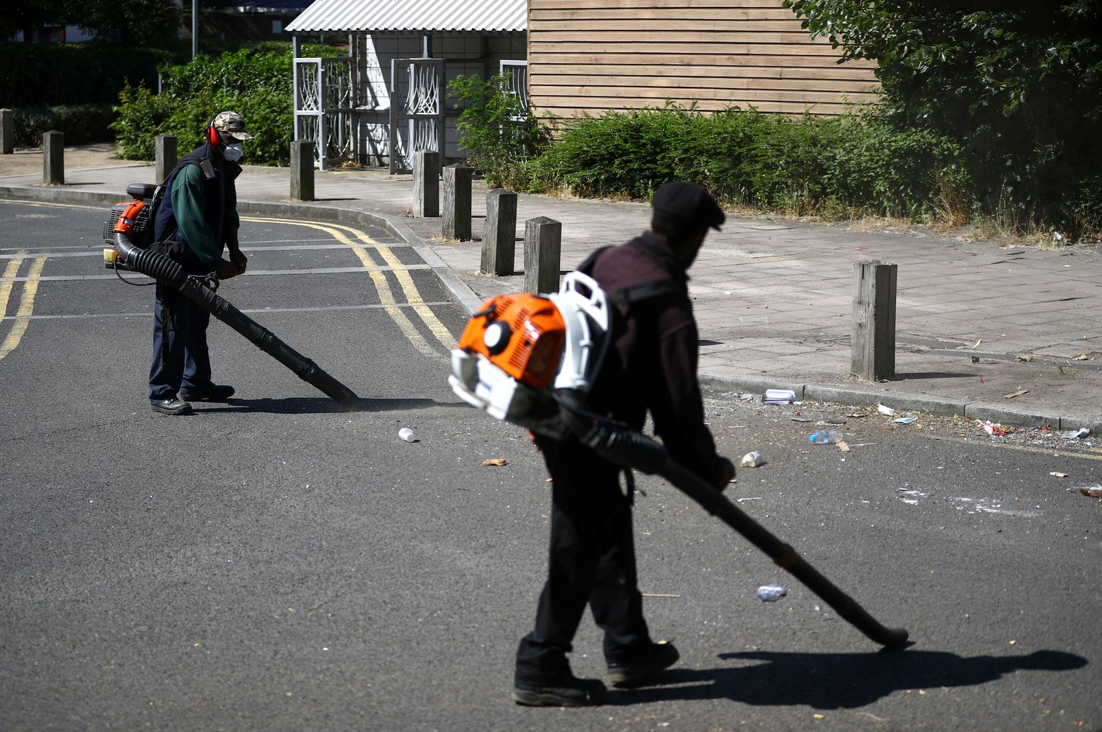 Workers clean rubbish from the street at Angell Town estate in Brixton