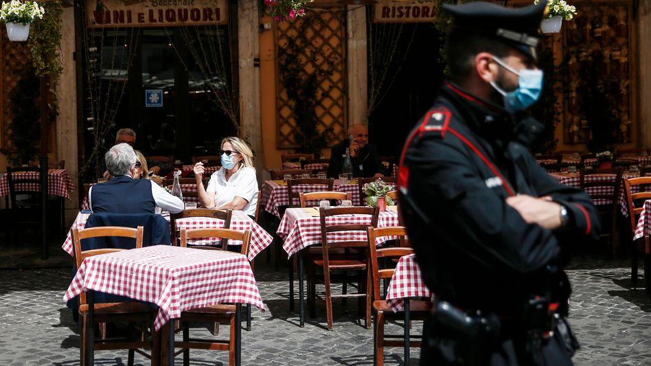 Ein Polizist in Rom patrouilliert vor den Tischen im Außenbereich eines Restaurants