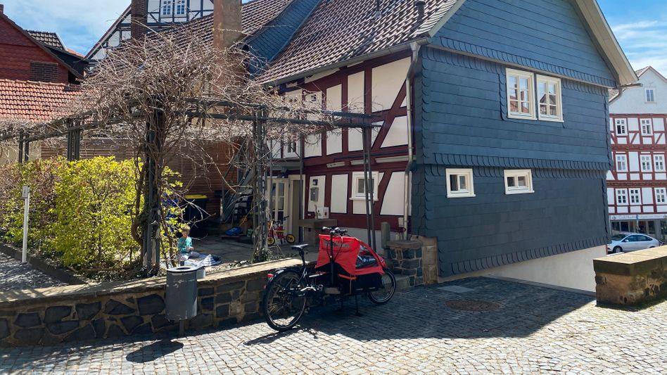 Lastenrad vor Fachwerkhäuschen – eine ideale Kombi, finden Anna und Tobias. Vom Ausflug bis zum Einkauf für die vierköpfige Familie erledigen sie in Homberg (Efze) alles damit.