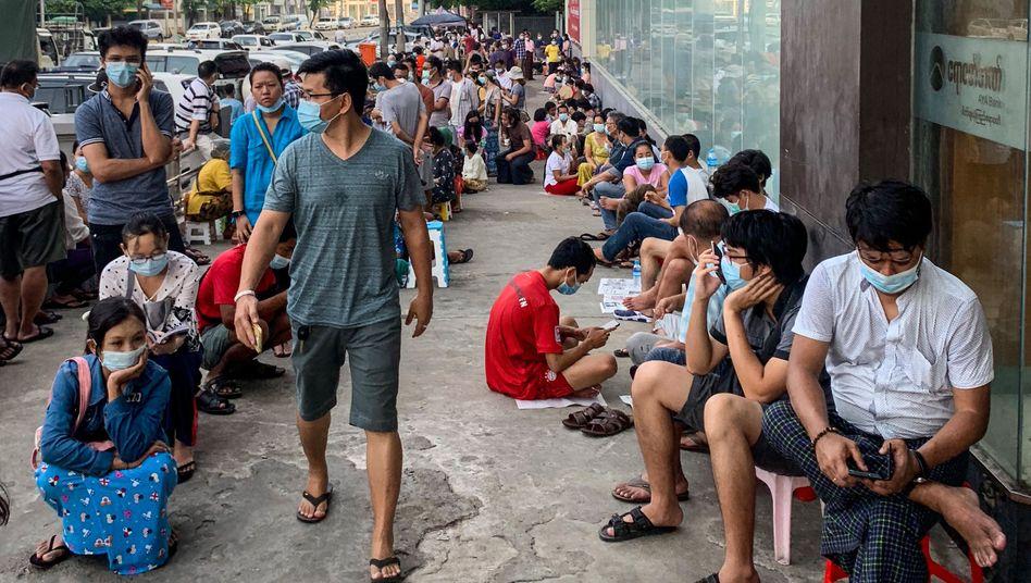 Wartende vor einer Bank in Myanmar