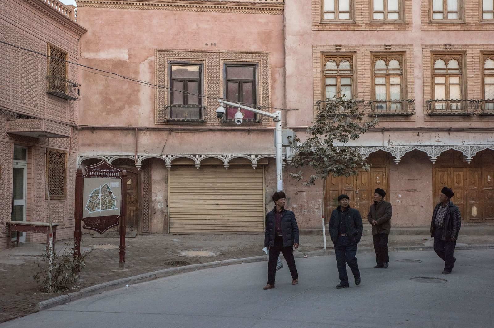 Men pass by surveillance cameras in Kashgar, China.