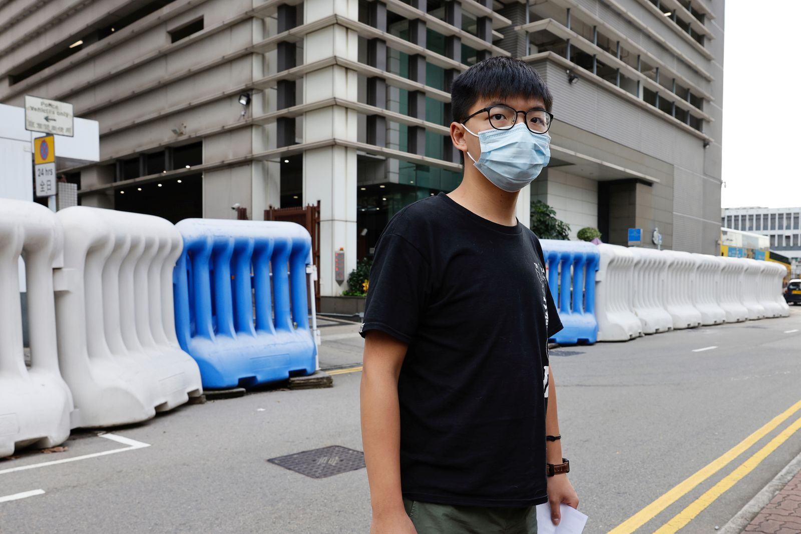 Pro-democracy activist Joshua Wong leaves a police station after being arrested for participating in an unauthorized assembly last year, in Hong Kong