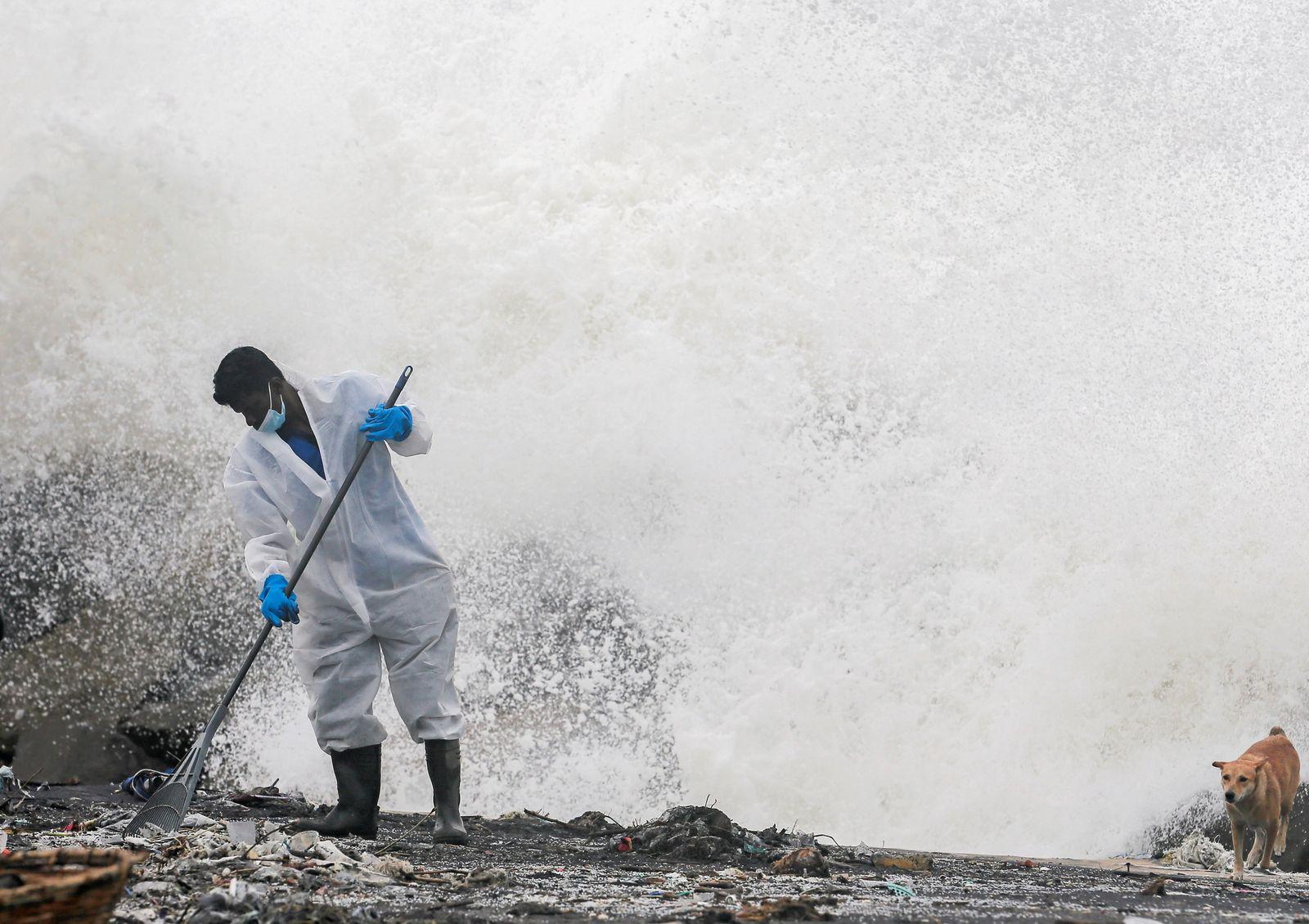Sri Lankan navy members remove debris washed to beach from MV X-Press Pearl, in Ja-Ela