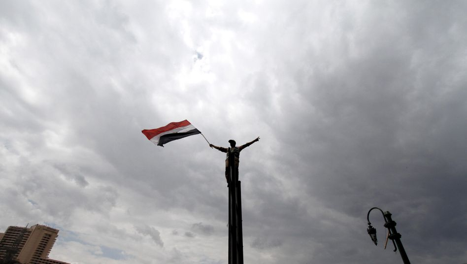 An Egyptian protester waves a flag at a weekly anti-Mubarak demonstration in Tahrir Square in Cairo, Egypt in April.