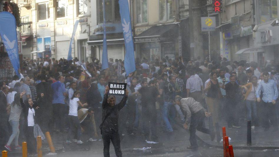 """Die Polizei setzt Wasserwerfer ein: Ein Demonstrant hält in Istanbul ein Schild mit der Aufschrift """"Friendensblock"""" hoch"""