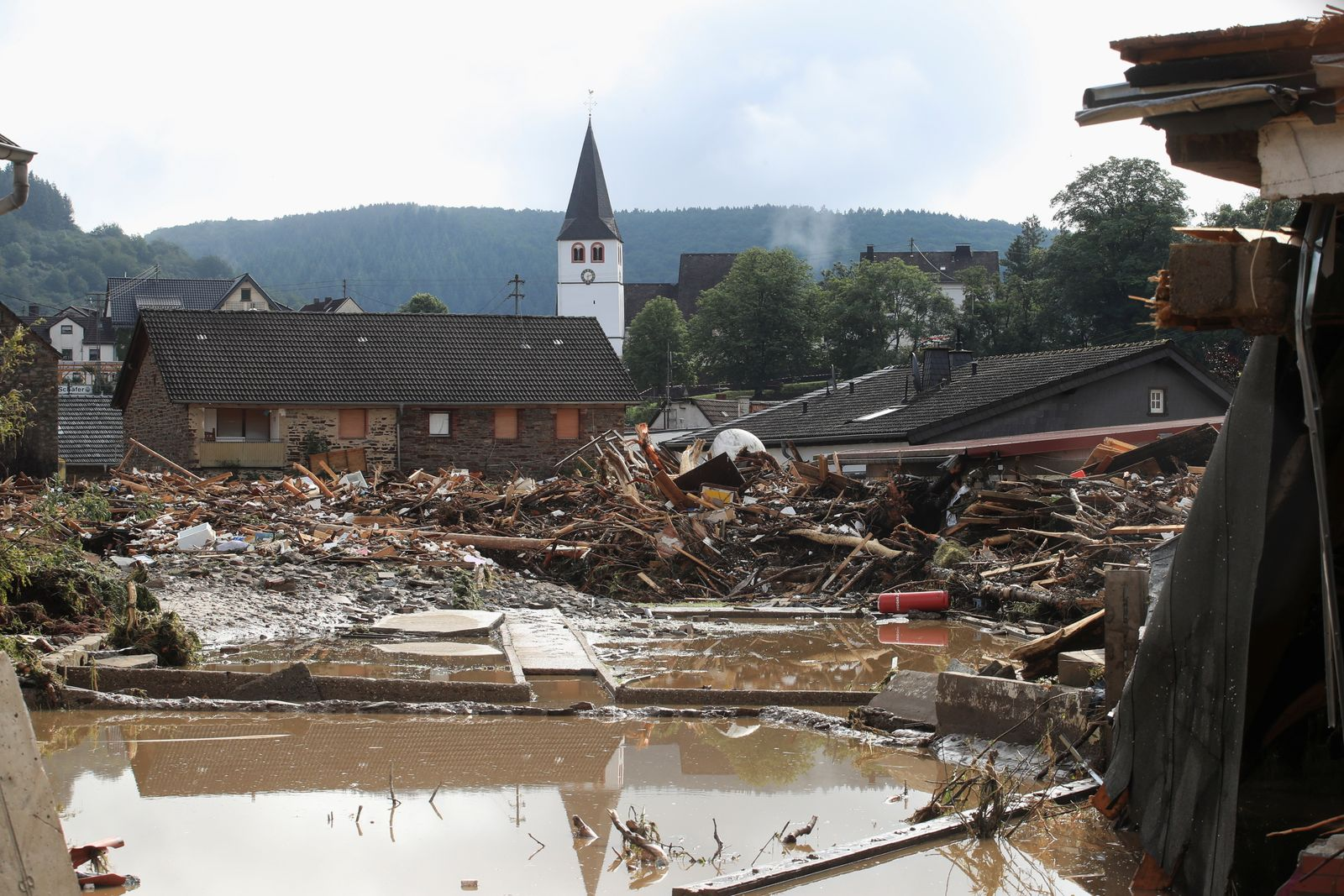 Collapsed houses are seen on a flood-affected area following heavy rainfalls in Schuld