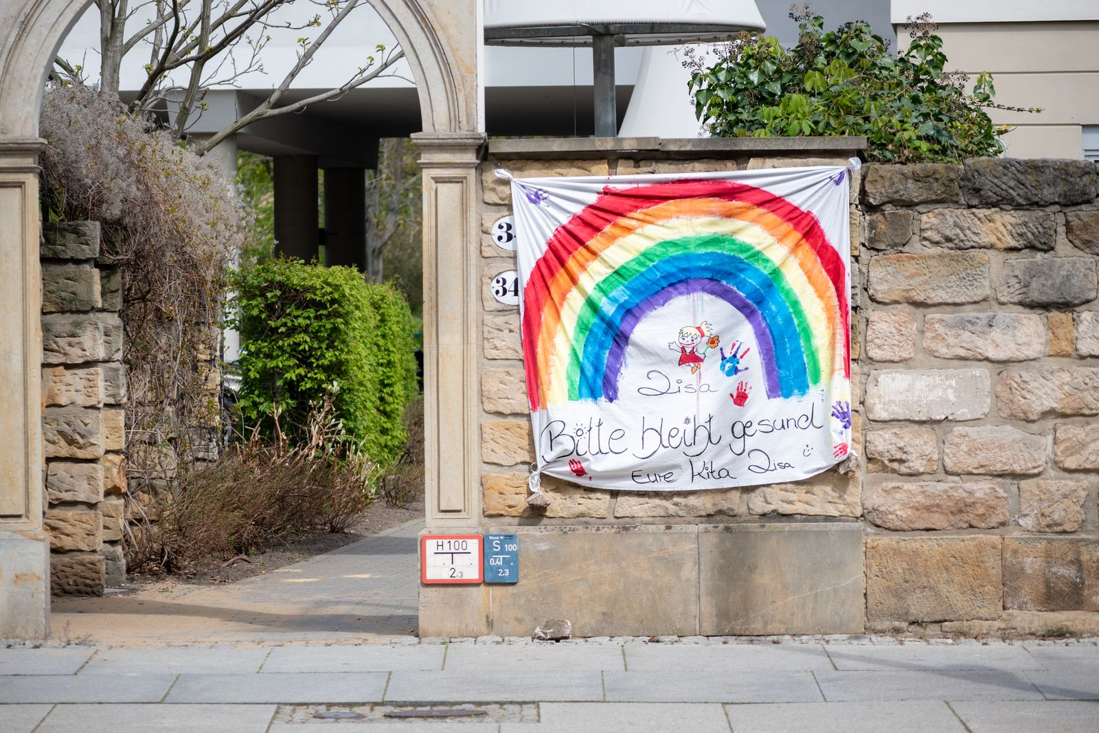"Flag hanging outside a kindergarten with a German inscription ""Please stay healthy, her kita Lisa"", with a rainbow drawn."