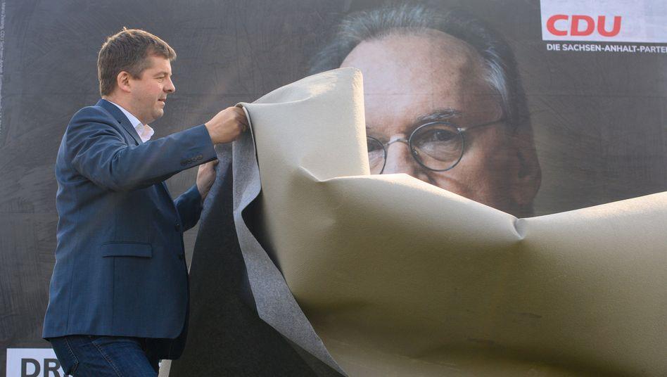Sven Schulze, Vorsitzender der CDU Sachsen-Anhalt, enthüllt ein Wahlplakat mit einem Porträt des Ministerpräsidenten Rainer Haseloff (CDU)