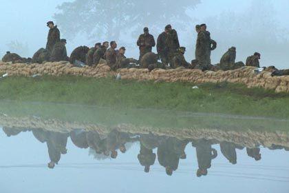 Erschöpft: Bundeswehrsoldaten auf einem Deich bei Dannenberg nach einem 12-stündigen Arbeitseinsatz