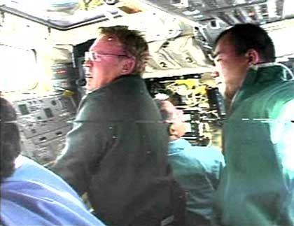 """""""Discovery""""-Astronauten Andy Thomas (l.) und Soichi Noguchi suchen mit einer Laserkamera am Roboterarm nach Schäden an der Außenhülle"""