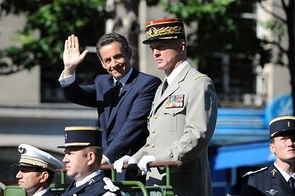 French President Nicolas Sarkozy (L) tries to ignore the morning's uprisings, waving to the crowd during the Bastille Day parade in Paris.