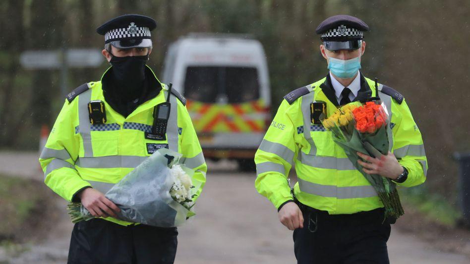 Ashford: Polizisten nehmen Blumen Trauernder entgegen, nachdem bei der Suche nach Sarah E. menschliche Überreste gefunden wurden