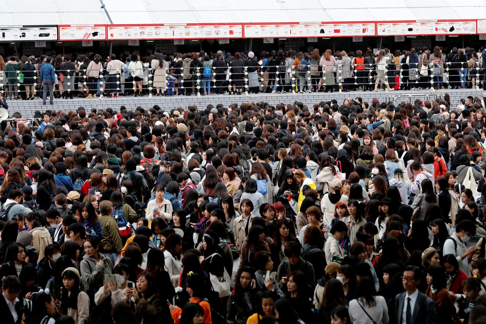 Fans of South Korean boy band BTS stand in a line in front of a booth selling BTS merchandise outside Tokyo Dome where the band's concert will be held in Tokyo