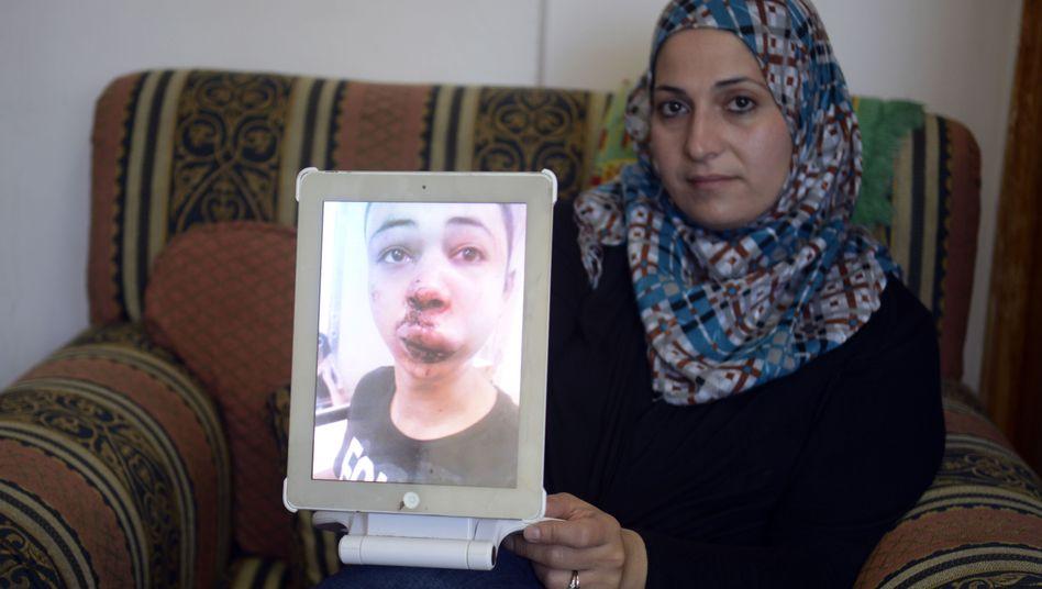 Die Mutter zeigt ein Bild ihres Sohns: Tarik soll von israelischen Grenzbeamten verprügelt worden sein