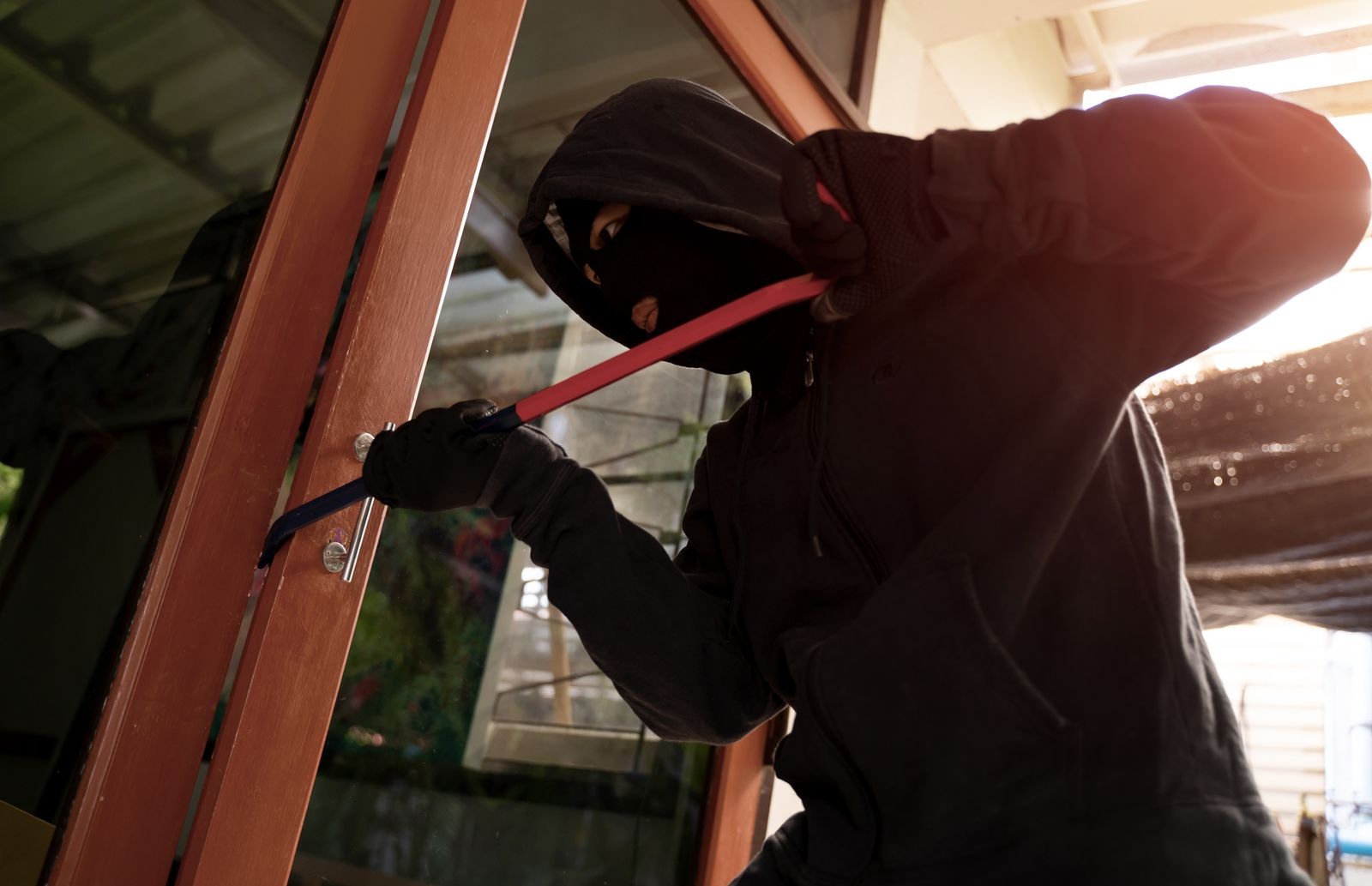 Male burglar wearing a hoodie forcing entry into a house with crowbar through a front door.