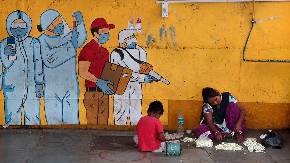 Straßenverkäuferin mit ihrem Sohn im indischen Mumbai