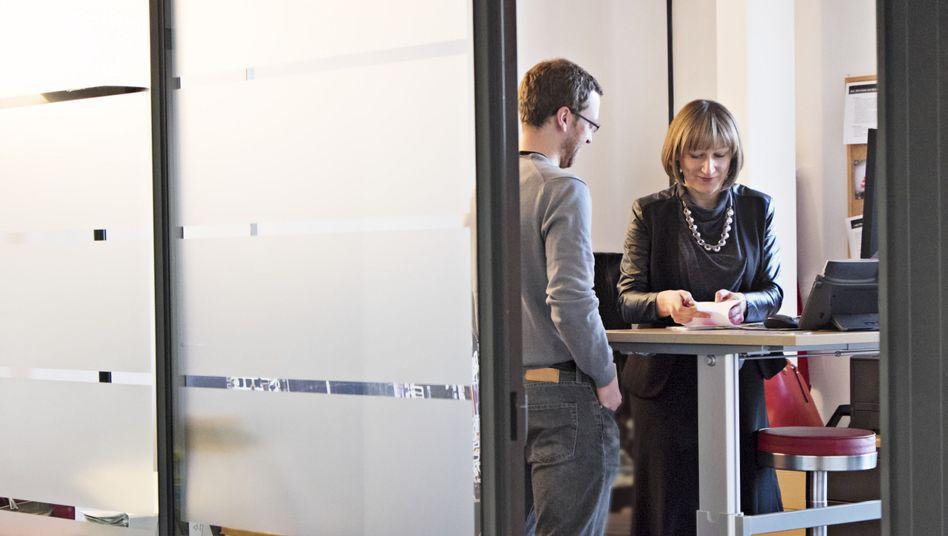 Kollegen am Stehtisch: Schützt Stehen im Büro vor Herz-Kreislauf-Erkrankungen?