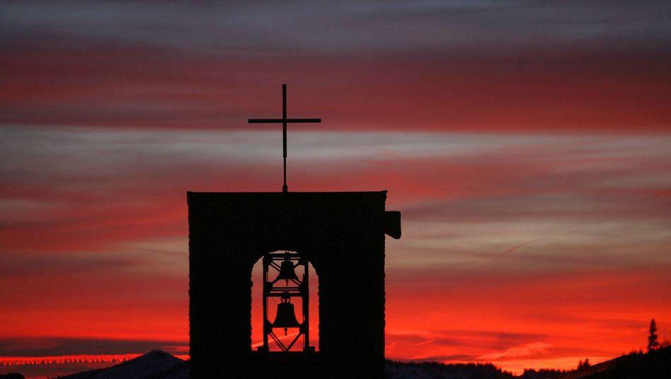 Kirche: Sonnenuntergang hinter dem Glockenturm der Heilig-Geist-Kirche in Oberjoch (Oberallgäu)