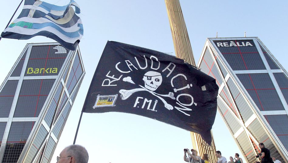 """A protester waves a flag reading """"fundraising for the IMF"""" at a demonstration in front of Madrid's Bankia bank."""