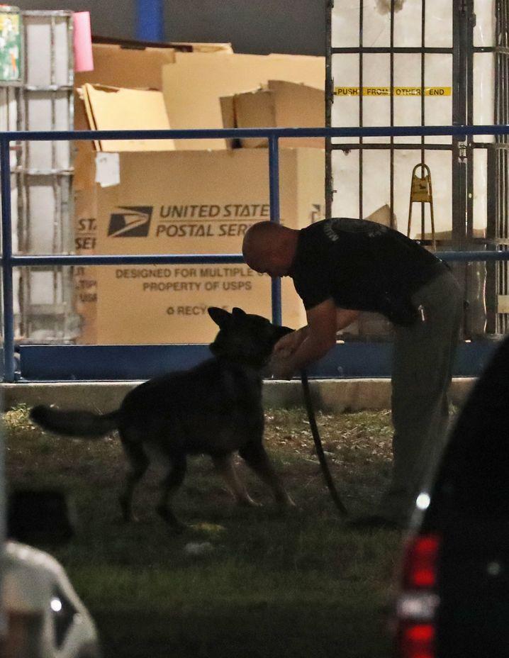 Polizist mit Hund vor dem Postverteilzentrums in Opa-locka