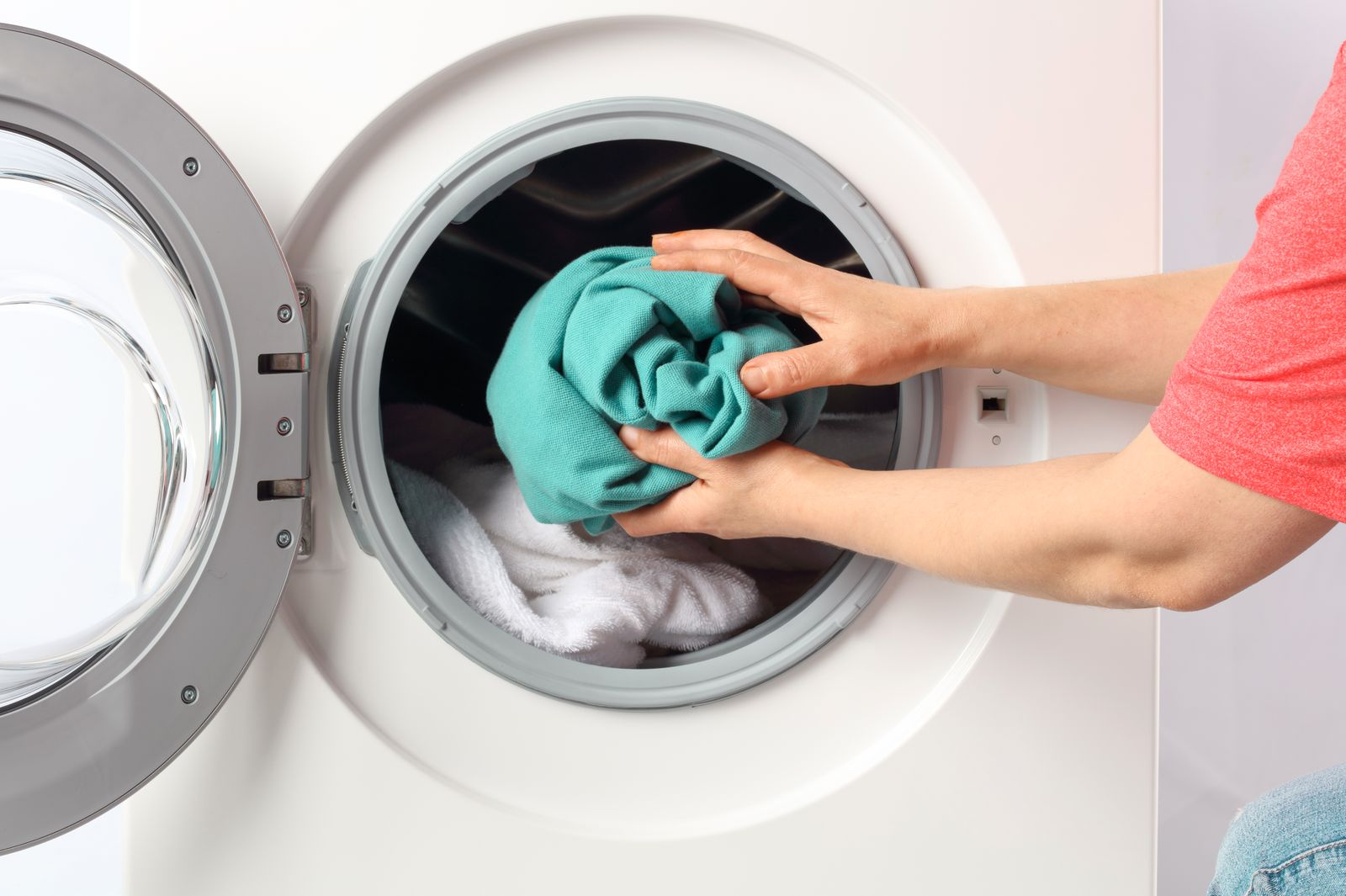 Cropped Hands Of Man Putting Clothes In Washing Machine At Home