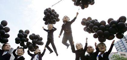 Aktivisten von Oxfam lassen Ballons steigen, an denen die Puppen der G-8-Staats- und Regierungschefs hängen