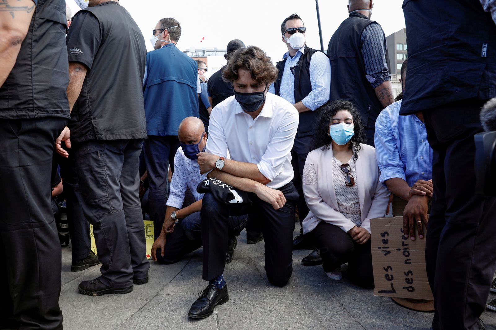 Canada's Prime Minister Justin Trudeau wears a mask as he takes a knee during a rally against the death in Minneapolis police custody of George Floyd, on Parliament Hill, in Ottawa