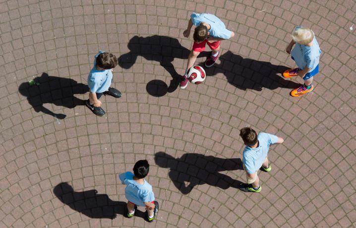 Schulkinder spielen Fußball auf dem Pausenhof