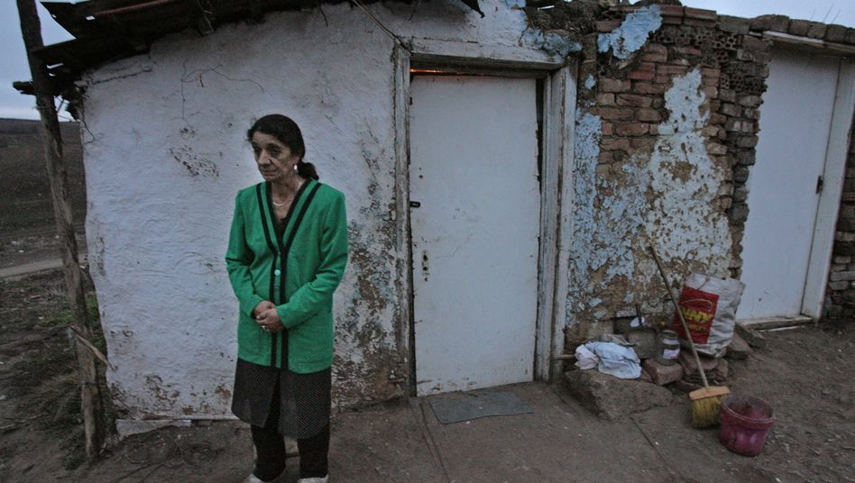 A Roma woman standing in front of her home in a village in Hungary.