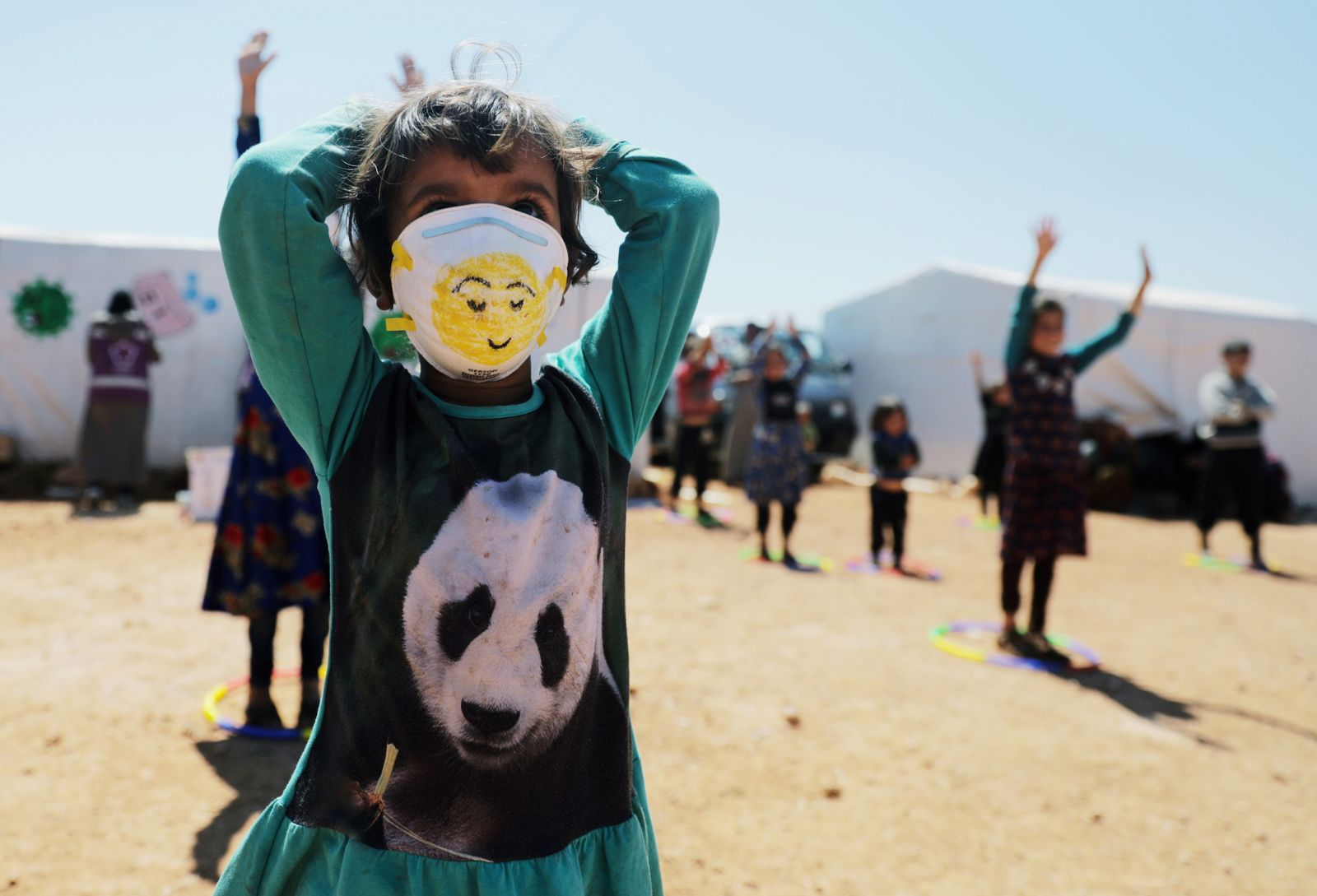 A displaced girl wears a face mask as she takes part in an event organzied by Violet Organization