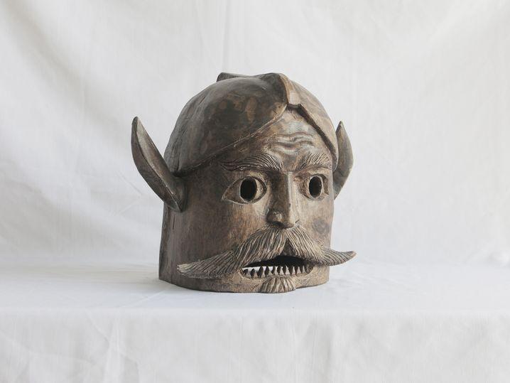 Masken symbolisieren verschiedene Episoden der Kolonialgeschichte