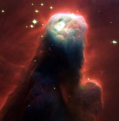 Ungeheuer aus Gas und Staub: Der Nebel NGC 2264 im Sternbild Einhorn präsentiert sich als gigantische Säule mit leuchtend rotem Rand. Das monströse Gebilde wurde von der Strahlung junger und heißer Sterne über Millionen von Jahren aus interstellaren Gasmassen herausgemeißelt. Wie der berühmte Adlernebel ist auch NGC 2264 eine Sterngeburtsstätte: In seinen dichtesten Regionen, die der Strahlung am längsten standhalten, können sich Sonnen und Planeten zusammenballen.
