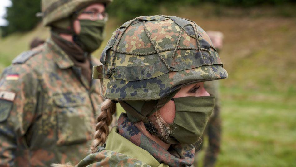 Soldatin und Soldat mit Helm und Mund-Nasen-Schutz während einer Luftverteidigungsübung