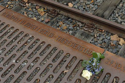 """A rose lies on the """"Platform 17"""" monument outside Berlin to the Jews taken to the concentration camps by rail."""