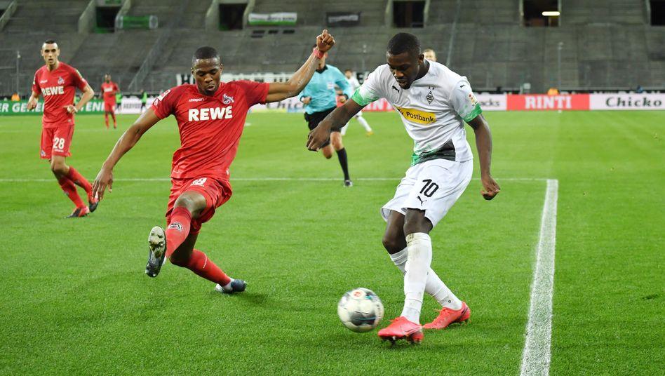 Marcus Thuram von Mönchengladbach im Zweikampf mit Kölns Kingsley Ehizibue