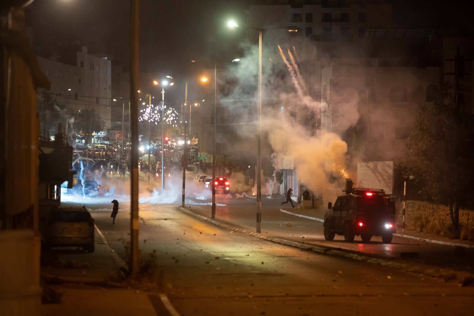 (210511) -- BETHLEHEM, May 11, 2021 -- An Israeli military vehicle fires tear gas canisters at Palestinian protesters d