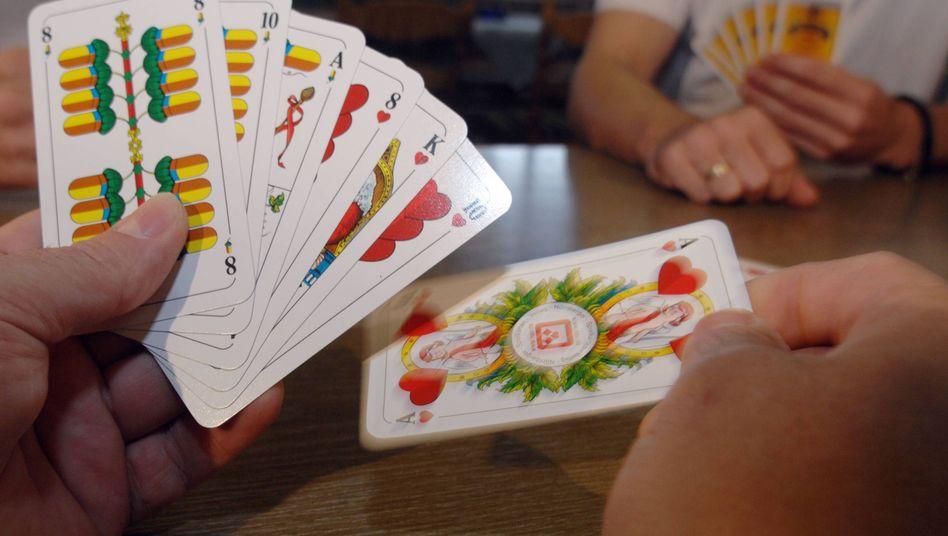 Kartenspieler hält Schafkopf-Spielkarten in der Hand
