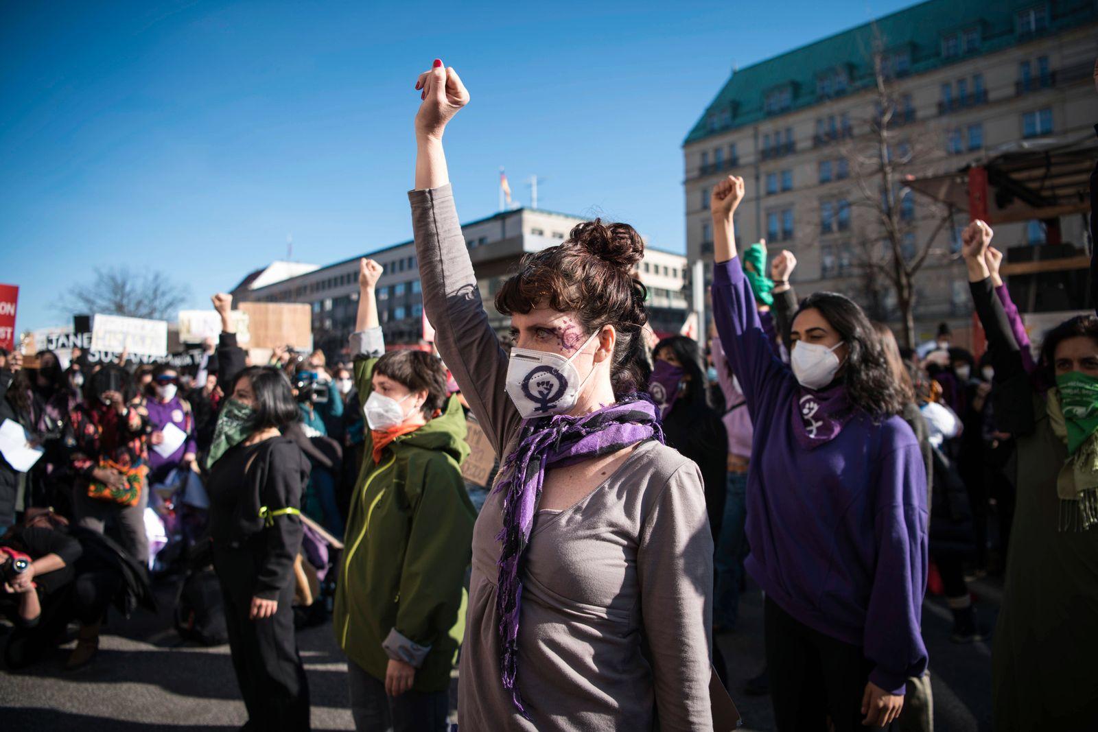 Demonstrantinnen auf der Frauentagsdemo am 8. März 2021 vor dem Brandenburger Tor strecken die Faeuste in die Luft. Foto