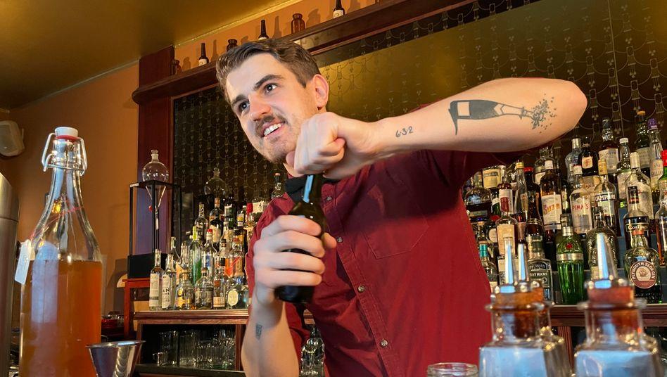 Während er eine Getränkebestellung bearbeitet, plaudert Barkeeper Dominik Köhler per Videoanruf mit seinen Gästen