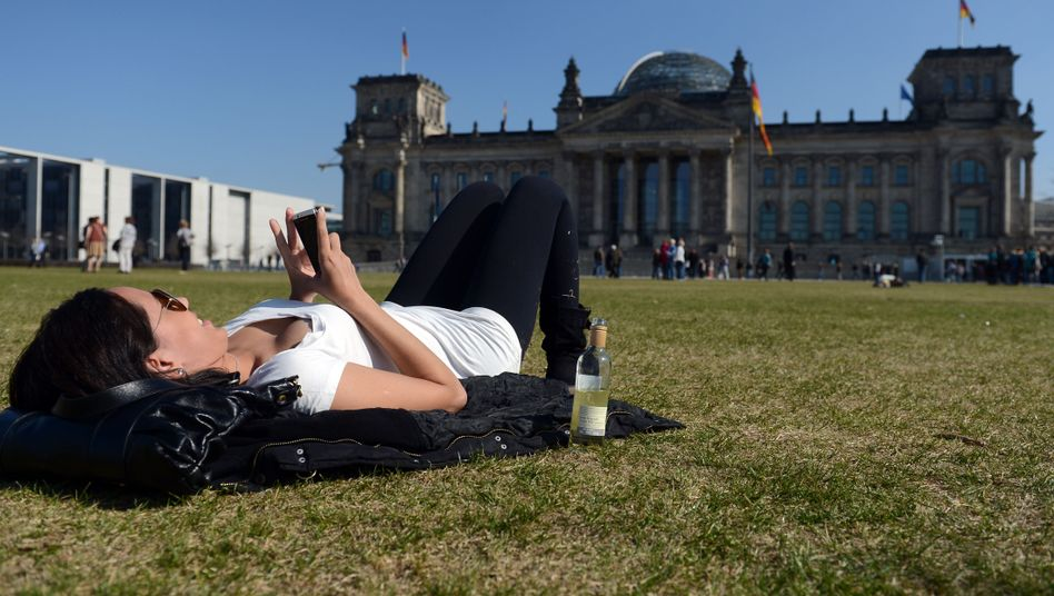 A young woman checks her phone outside Germany's parliament building, the Bundestag.
