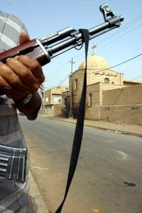 Ein irakischer Wachmann bewacht eine der angegriffenen Kirchen