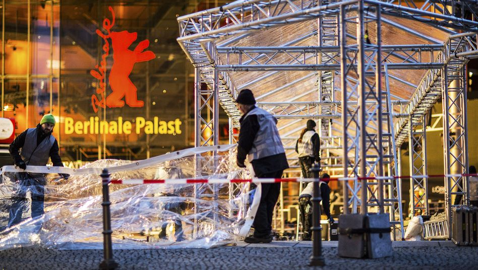 Workers mount temporary roofage in front of the Berlinale Palace, where 19 films will be competing for the top prize, the Golden Bear.