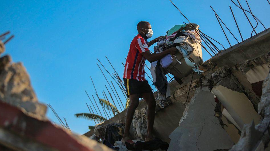 Tausende Menschen auf den Straßen: Ein Bewohner von Les Cayes, Haiti, holt Gegenstände aus seinem zerstörten Haus