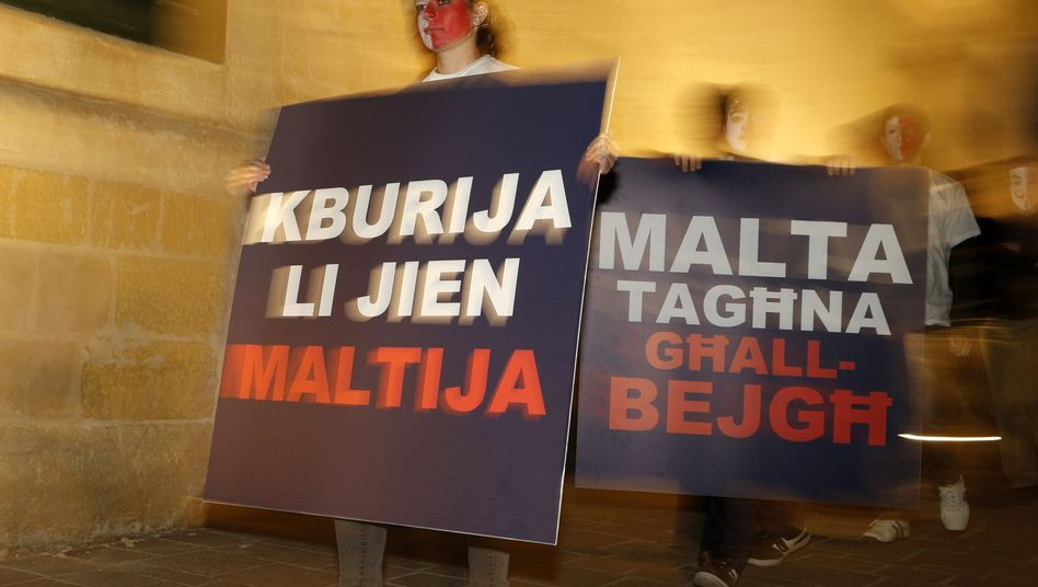 Protesters in Valetta express their opposition to a new law that allows foreigners to buy Maltese passports.
