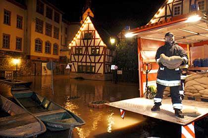 In Seligenstadt schichten Feuerwehrmänner Sandsäcke auf. Die Altstadt droht vom Main überflutet zu werden